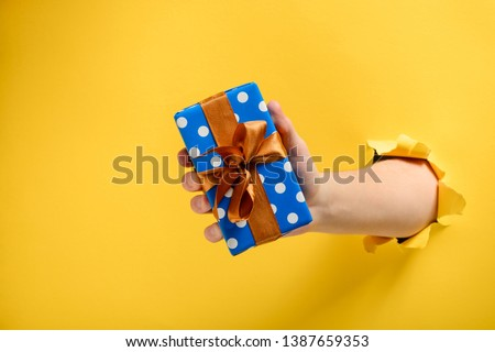 Hand giving a gift box through torn yellow paper wall. Polka dot package and satin ribbon bow. Special offer or sale concept.