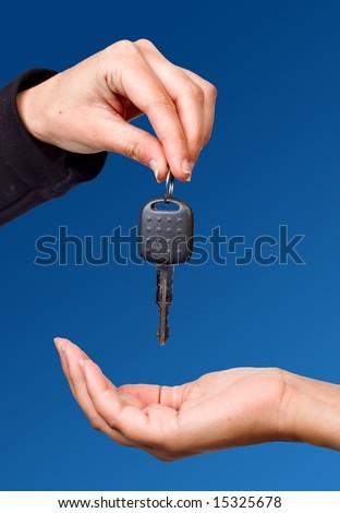 Hand giving a key over blue sky