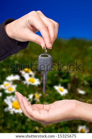 Hand giving a key over nature background