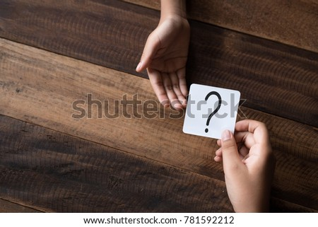 hand giving a note written question mark. asking question concept #781592212