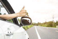 hand giving a thumbs up sign throw the window of a car parked near the roads.The symbol of a hand raised for help.when the car is broken.