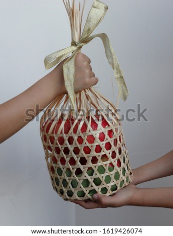 Hand giving fresh fruit basket to friend, closeup. Give and take concept.