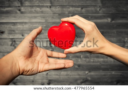Hand giving hand a red heart.