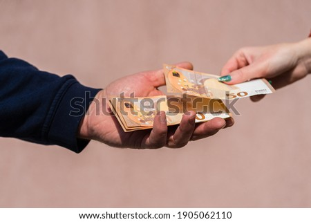Hand giving money like bribe or tips or salary isolated, hard worked hand taking euro banknotes. Currency transfer and reward for hard work. Foto d'archivio ©