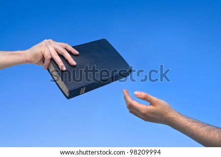 Hand giving the Bible to another person