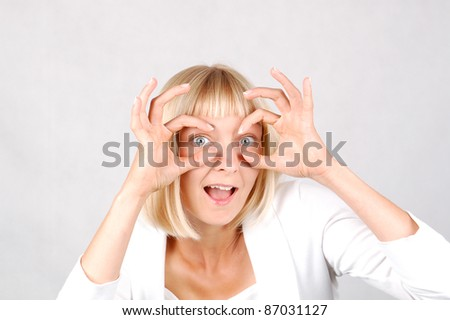Hand Glasses/Young Woman puts on a pair of hand glasses and looks at the camera with astonishment