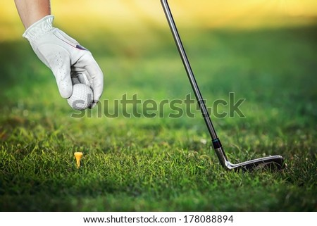 Hand golfers as gives the ground a golf ball on the tees