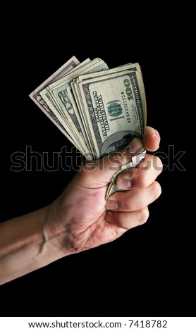 Hand grasping American money isolated on black
