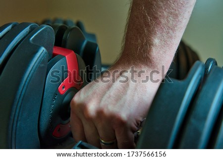 Hand gripping adjustable dumbbells for working out at home. male hand with ring visible. Foto stock ©