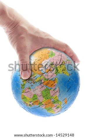 Hand gripping globe showing Africa, Europe and Asia