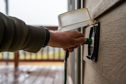 Hand gripping power cord and lifting cover of an outdoor GCFI outlet to plugin