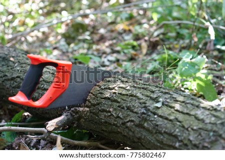 Hand hacksaw on wood cutting of tree on a natural background