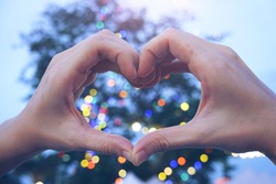 hand heart shape with blurred night light,defocus, bokeh,night market concept,beautiful circle glitter Christmas and happy new year and love celebrating lamp dark sky festival dusk blurry flare