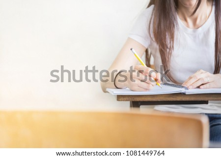 hand high school or university student in casual holding pencil writing on paper answer sheet.sitting on lecture chair taking final exam attending in examination room or classroom.