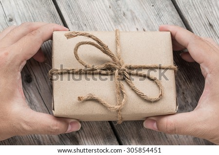 Hand hold A Vintage gift box brown paper wrapped with rope on wood background