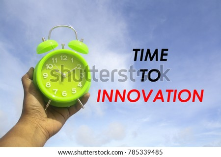 hand hold alarm clock with word time to innovation over sky background #785339485
