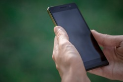 hand hold black smart phone, cell phone, mobile over blurred image of green forest background
