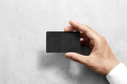 Hand hold blank black craft card mockup with rounded corners. Plain kraft call-card mock up template holding arm. Hand made namecard display front. Check offset card design. Business branding.