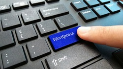 hand hold blue Wordpress keyboard button
