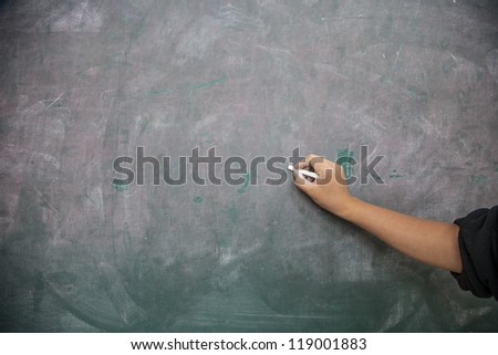 hand hold chalk start writing in the blackboard - stock photo