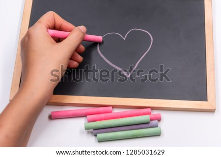 Hand hold color chalk draw cartoon heart shape on blackbroad.Tell love in valentine day or tell save good health and heart. #1285031629