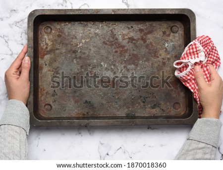 hand hold empty metal rectangular baking sheet on a white table, top view Foto d'archivio ©