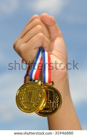 hand hold gold medal in blue sky background