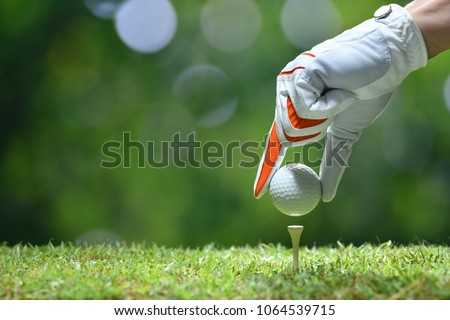 Hand hold golf ball with tee on golf course #1064539715