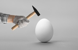 hand hold hammer and batter white chicken egg, on light grey background. Breakable or sturdy concept