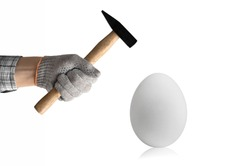 hand hold hammer and batter white chicken egg, on white background, isolated. Breakable or sturdy concept
