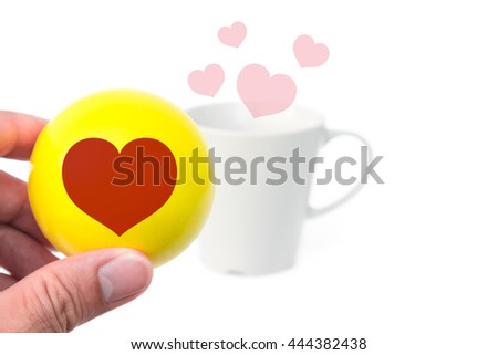 Hand hold heart shape on yellow  ball with coffee lover mug blur background, Happy concept, soft focus #444382438