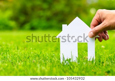 Hand hold house against green field - stock photo