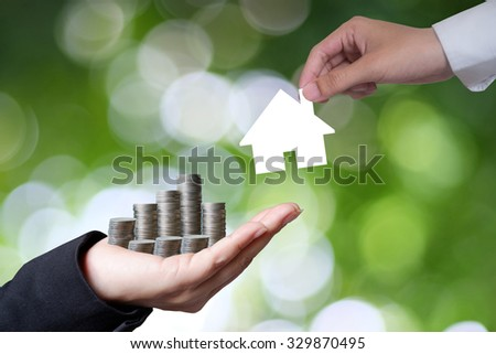 Hand hold money to change the house on green background , business idea and finance concept