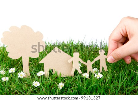 Hand hold paper cut  of family over  fresh spring green grass