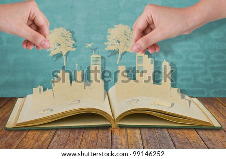 Hand hold paper cut  of tree over Paper cut of cities with car and plane on old book