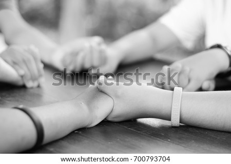 Hand hold Praying family. Father Mother daughter and son holding hand and pray in the table. black.