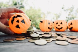 Hand hold pumpkin bucket, pouring gold coins money on wood table with miniature pumpkins box in blur natural tree