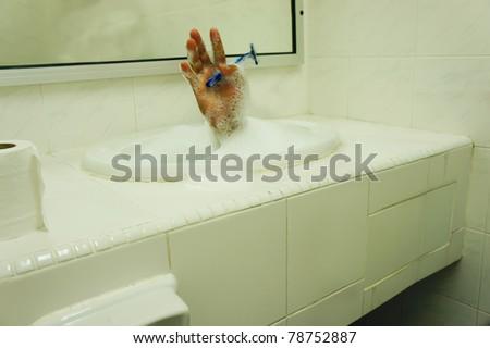 hand hold shaving in wet sink