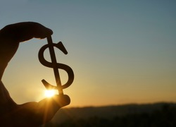 Hand hold silhouette of dollar sign , symbol of american money against sun rays and sunset sky with clouds. Dollar sign. empty copy space for inscription or other objects