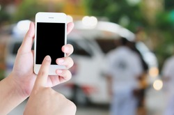 hand hold smartphone with Ambulance responding to an emergency call background