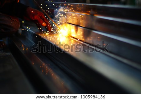Photo of Hand hold welding steel. Renovation wooden house to new construction. Welds with argon-arc welding. Selective focus and toned image. Free copy space.