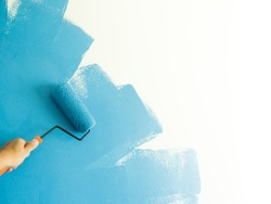 hand hold with painting roller with blue color
