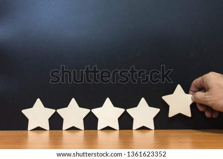 Hand hold Wood block five star shape on wooden table black background. Block 5 stars rated best service excellence concept. Excellence customer vote quality satisfaction winners award. #1361623352