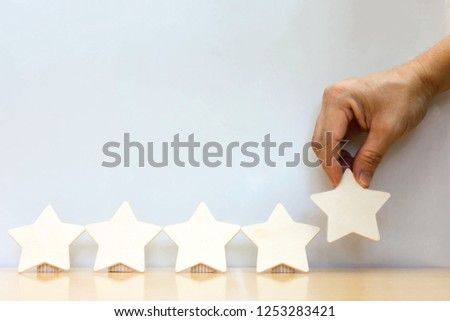 Hand hold Wood block five star shape on wooden table gray background. Block 5 stars rated best service excellence concept. Excellence customer vote quality satisfaction winners award. #1253283421