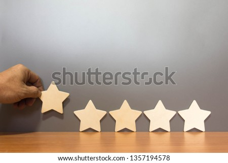 Hand hold Wood block five star shape on wooden table gray background. Block 5 stars rated best service excellence concept. Excellence customer vote quality satisfaction winners award. #1357194578