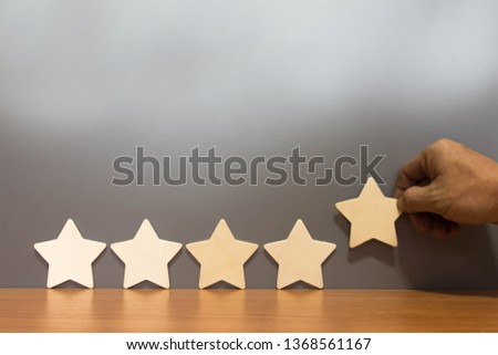 Hand hold Wood block five star shape on wooden table gray background. Block 5 stars rated best service excellence concept. Excellence customer vote quality satisfaction winners award. #1368561167