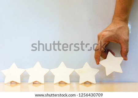 Hand hold Wood five star shape on wooden table gray background. Block 5 stars rated best service excellence concept. Excellence customer vote quality satisfaction winners award. #1256430709