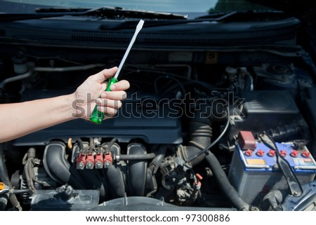 Hand hold wrenches for car repairs service in front of car engine