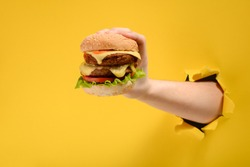 Hand holding a big burger through a hole in torn yellow paper wall. Special offer and cheap price on fast food.
