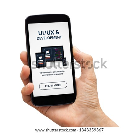 Hand holding a black smart phone with UI/UX design and development concept on screen. Isolated on white background. #1343359367